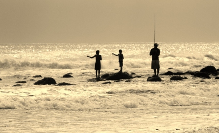 Kids fish with wire attached to wood while dad casts his line out